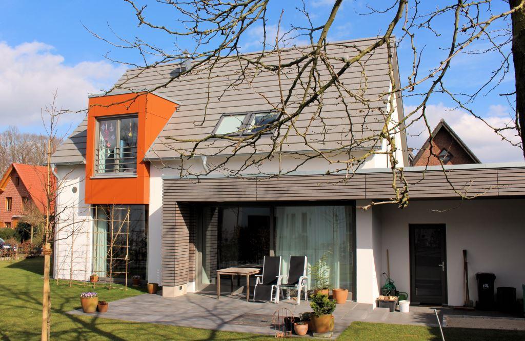 Holzhaus mit Putzfassade, Zwerchgiebel und Terrassenüberdachung