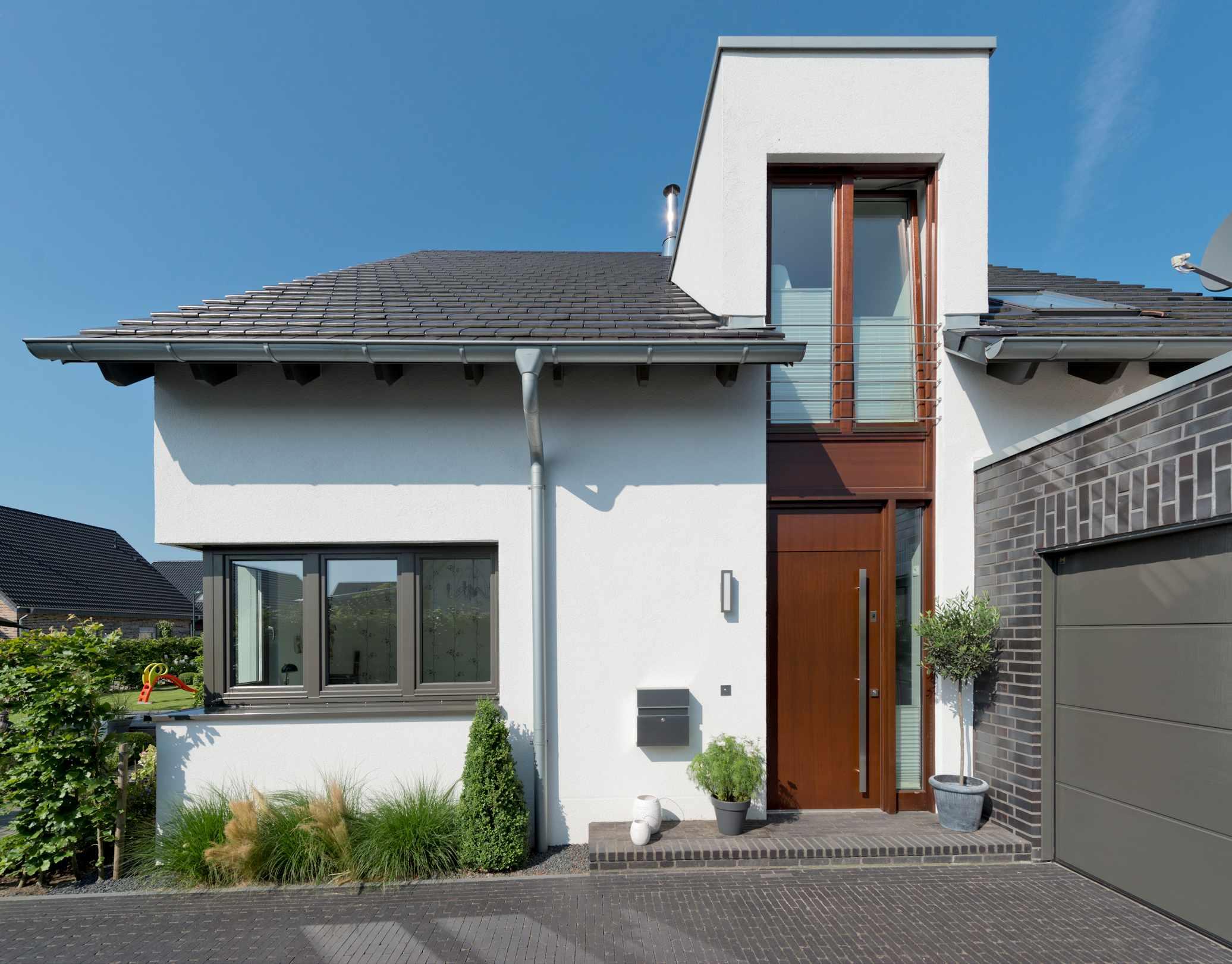 individuelles Holzhaus, Putzfassade, Zwerchgiebel, Haustüranlage