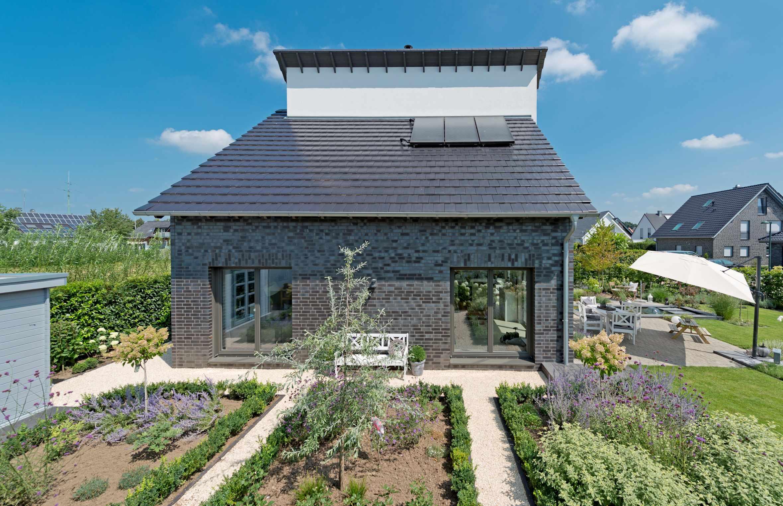 individuelles Holzhaus, Klinkerfassade, Putzfassade, gegenläufiges Satteldach