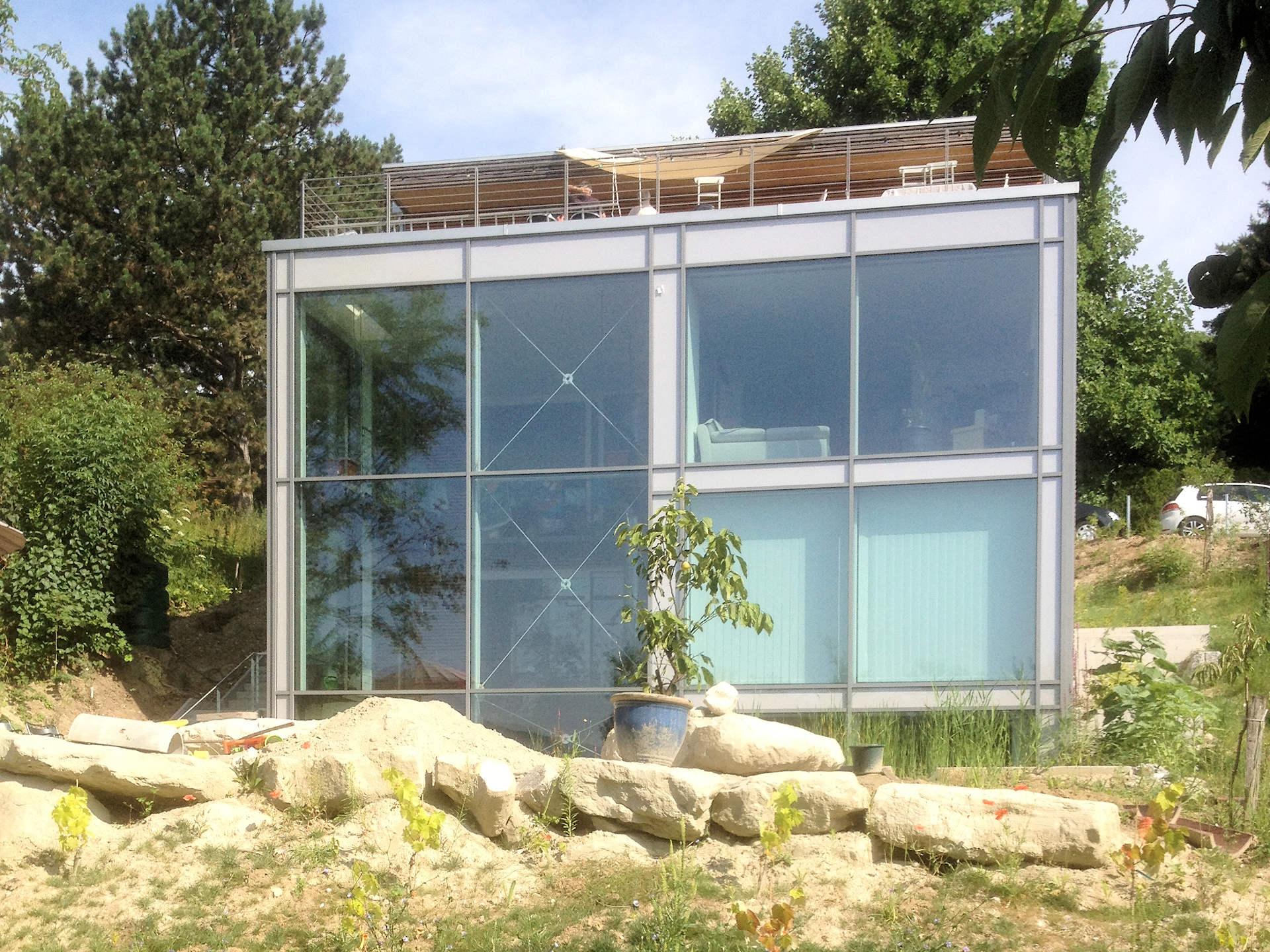 individuelles Holzhaus am Hang, Glasfront, Dachterrasse